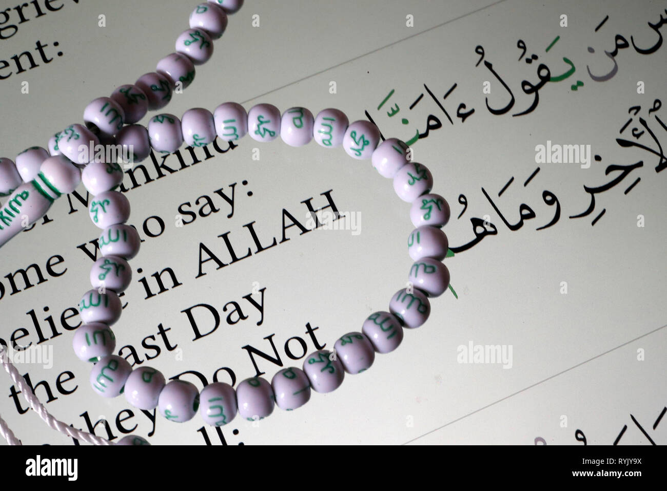 Digital Quran on a smartphone and muslim prayer beads.  English translation.  Believe in Allah.  Close-up. - Stock Image