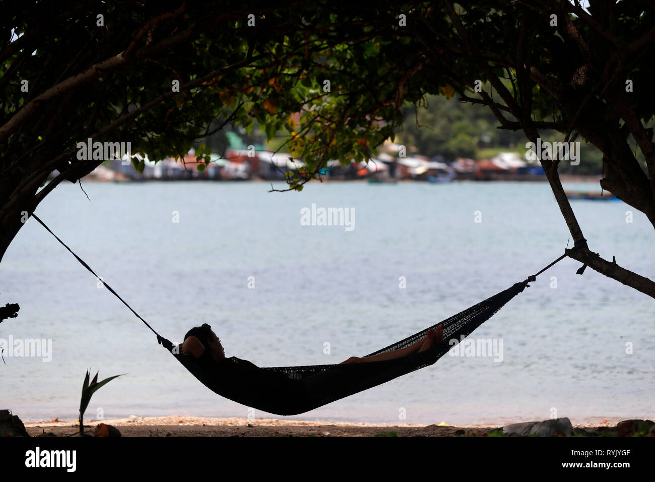 South China Sea. Woman relaxing on a beach  in a hammock.  Ha Tien. Vietnam. - Stock Image