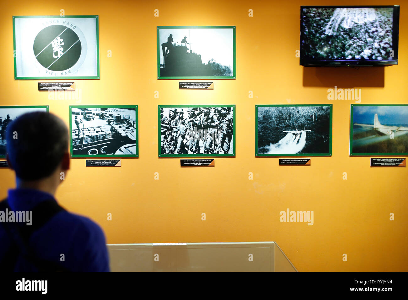 War Remnants Museum. Visitor looking at shocking photos from war.  Ho Chi Minh City. Vietnam. - Stock Image