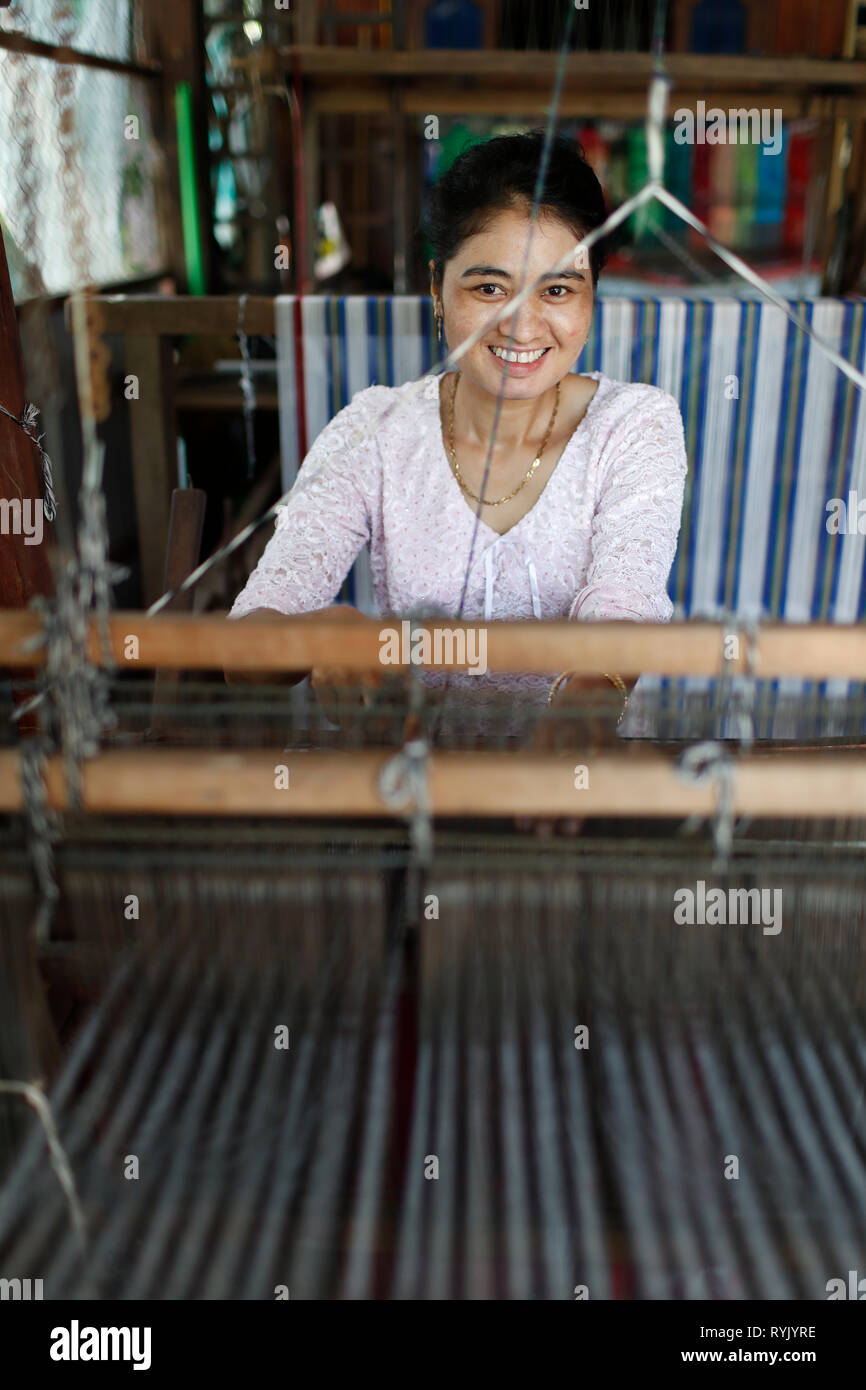 Traditional hand loom.  Local woman diligently weaving colourful scarves.  Chau Doc. Vietnam. - Stock Image