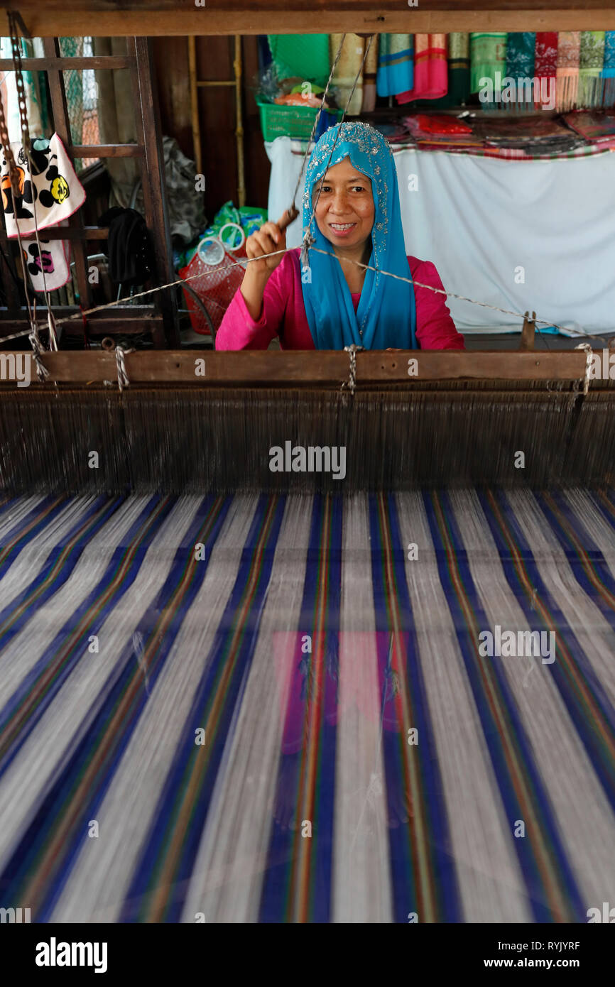 Traditional hand loom.  Local muslim woman diligently weaving colourful scarves.  Chau Doc. Vietnam. - Stock Image