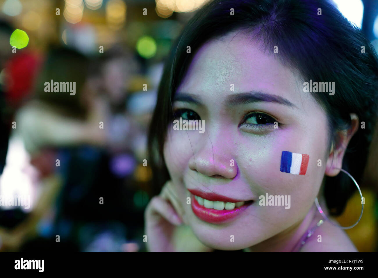 Smiling vietnamese woman with a french flag during the world football cup.  Ho Chi Minh City. Vietnam. - Stock Image