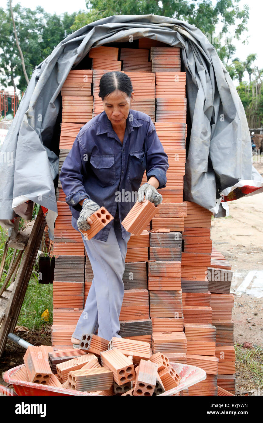 Woman working on construction site. Red bricks Vung Tau. Vietnam. - Stock Image