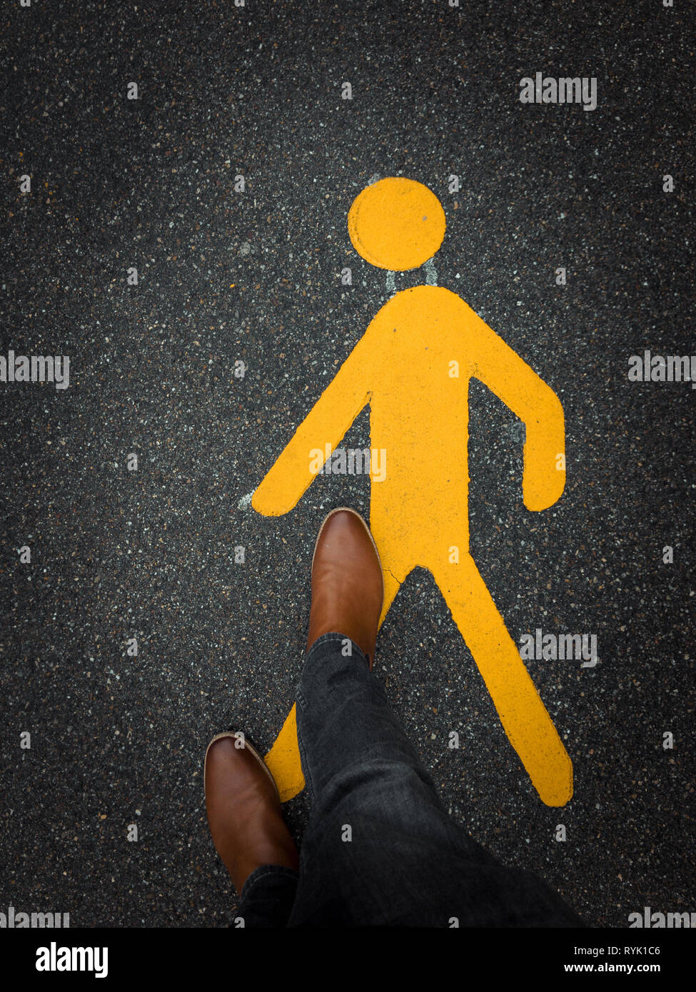 pedestrian sign on pavement with feet Stock Photo