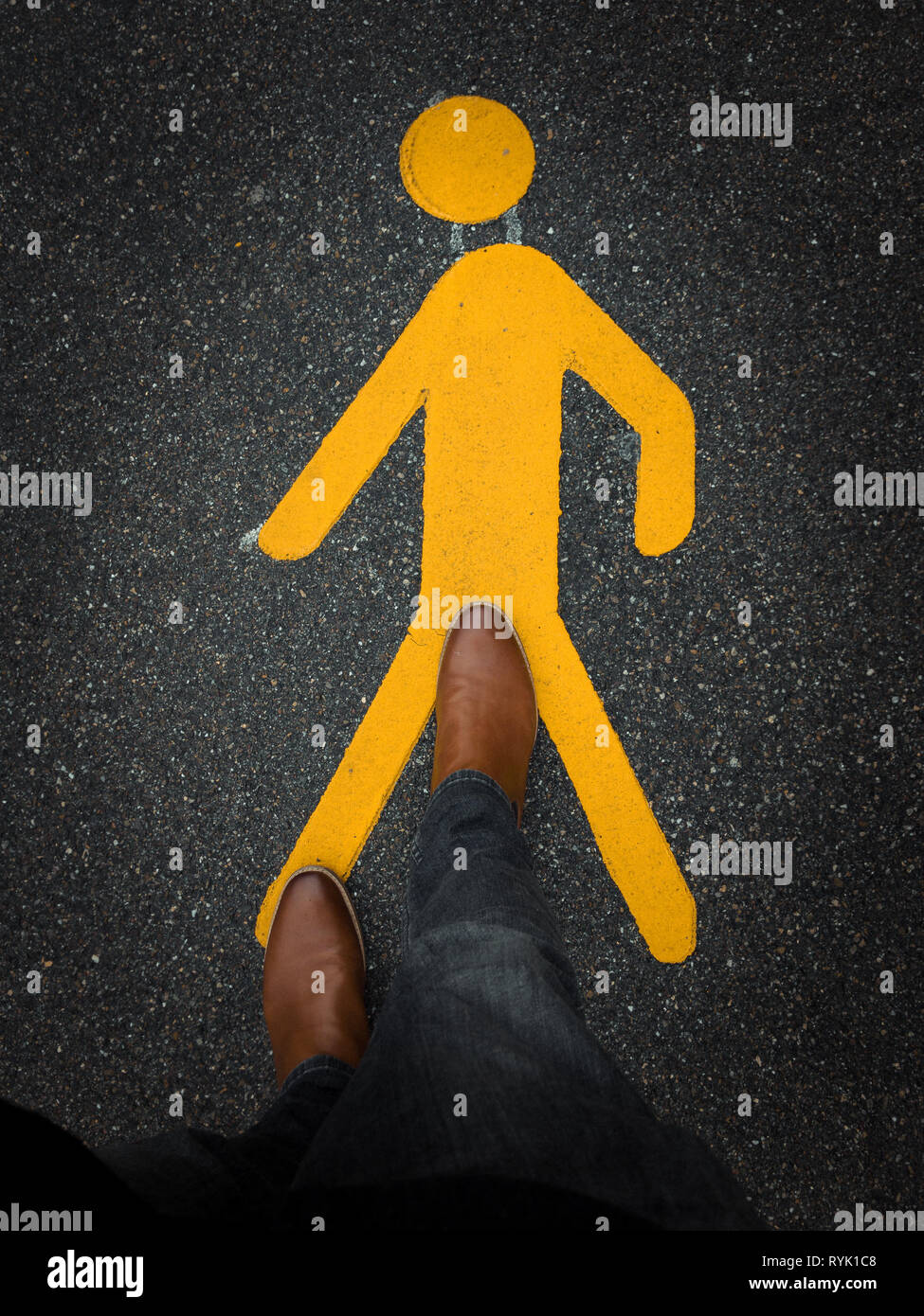 pedestrian sign on pavement with brown leather boot - Stock Image