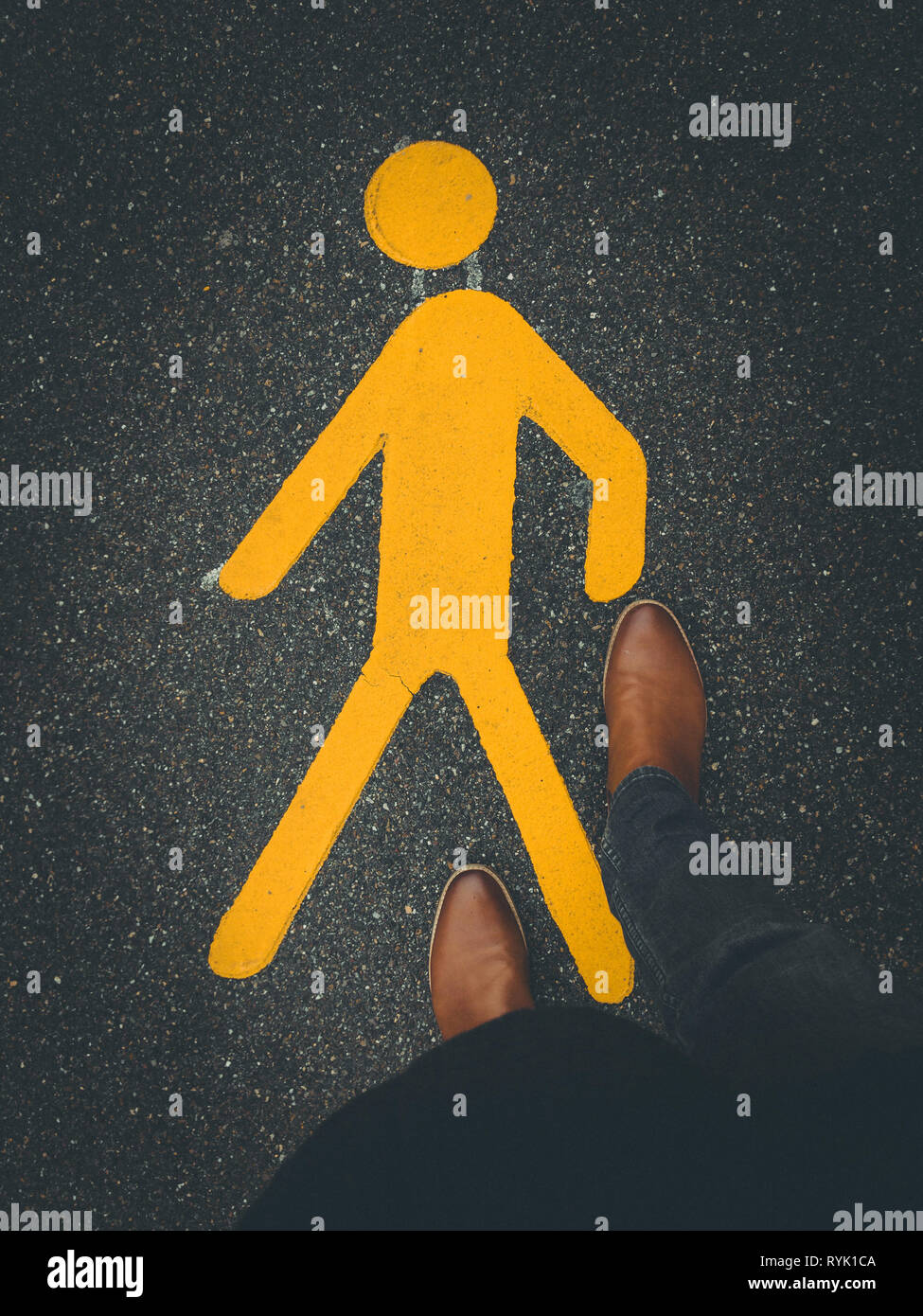 yellow pedestrian sign on pavement with feet - Stock Image