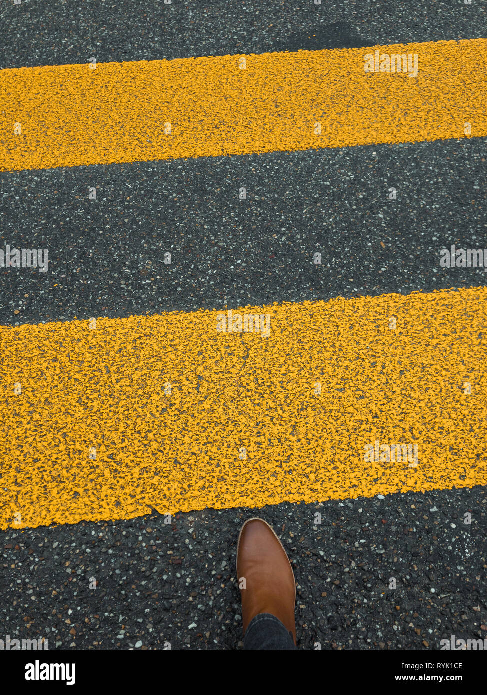 pedestrian stripe on pavement with feet - Stock Image