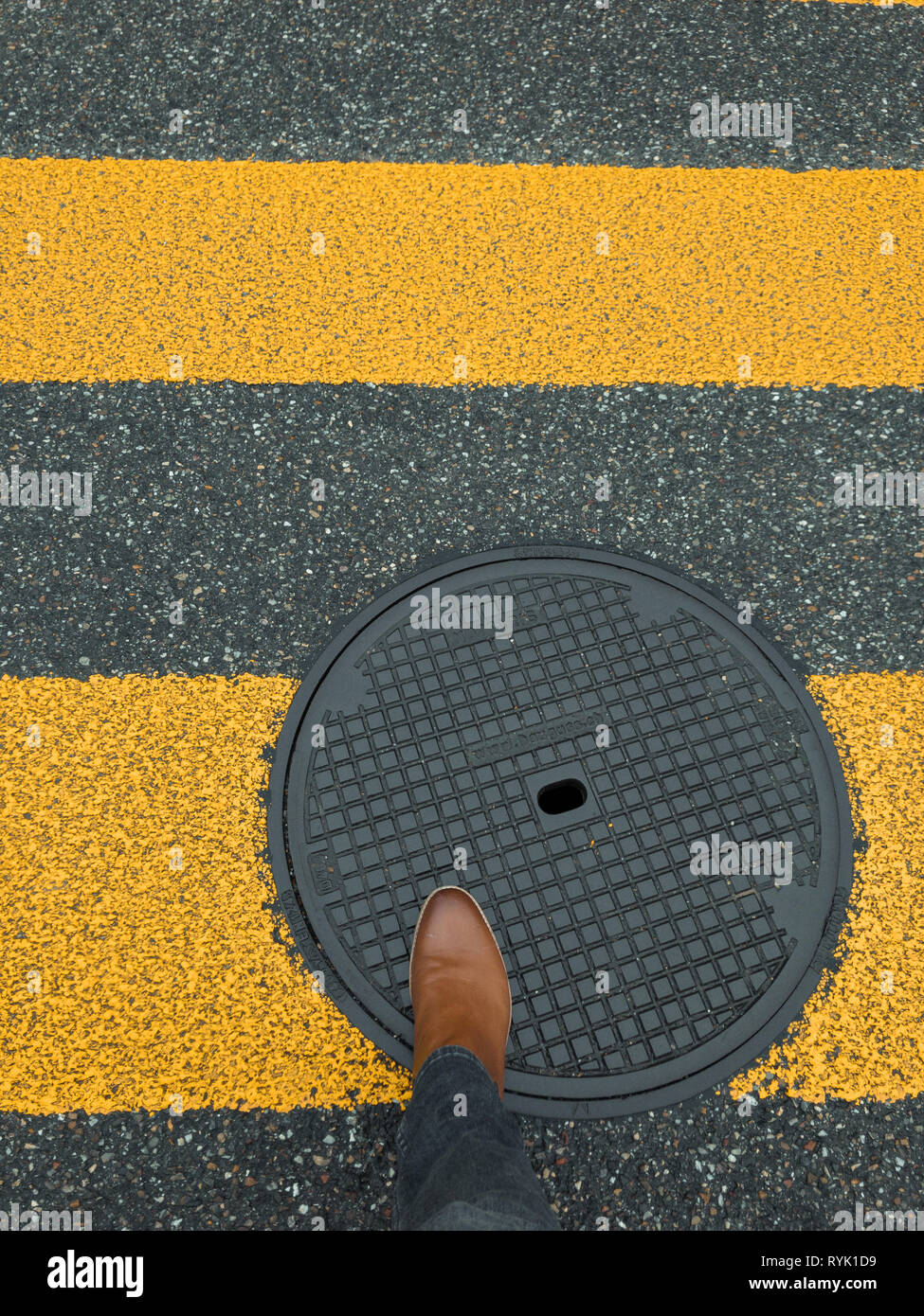 pedestrian sign on pavement with feet - Stock Image