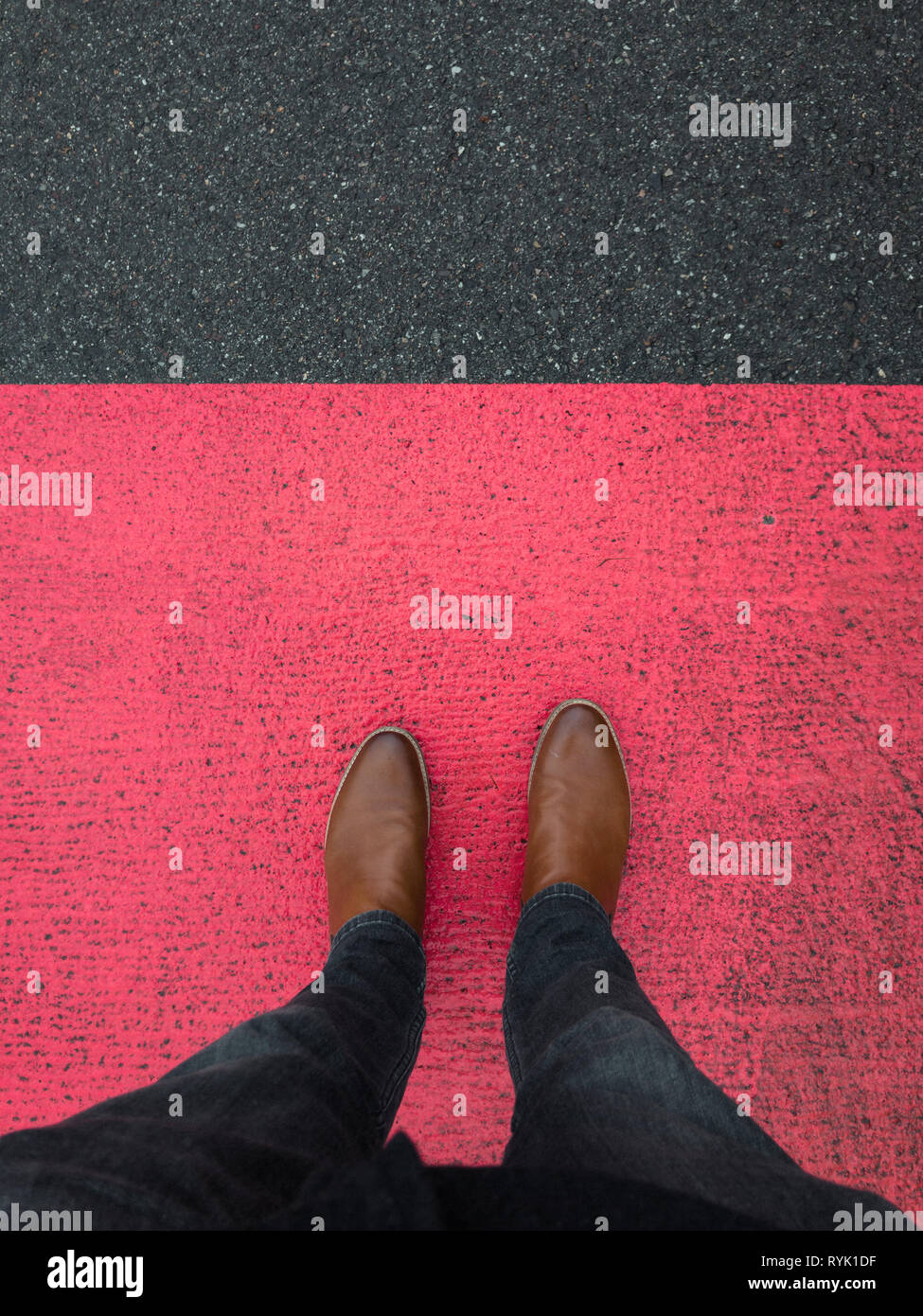 red marking on pavement with leather shoe - Stock Image