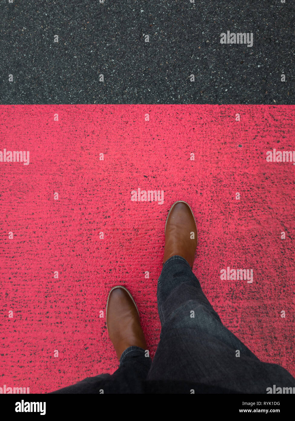 red marking on pavement with leather boot - Stock Image