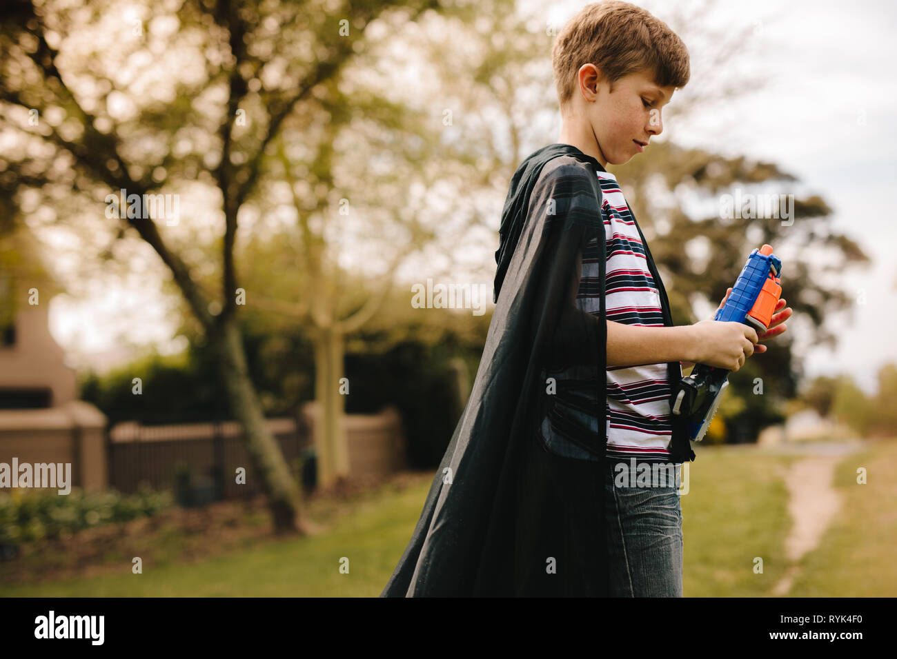 Side view of a young boys wearing a cape playing with toy gun outdoors. Boy with cape pretending to a superhero. - Stock Image