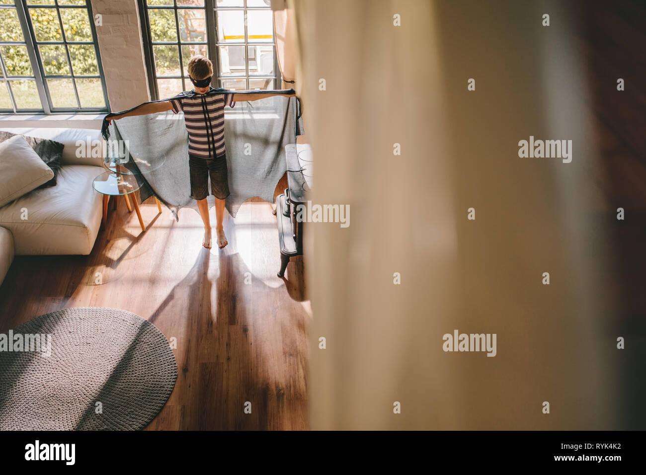 Boy pretending to a bat superhero. Boy playing in Bat costume at home. - Stock Image