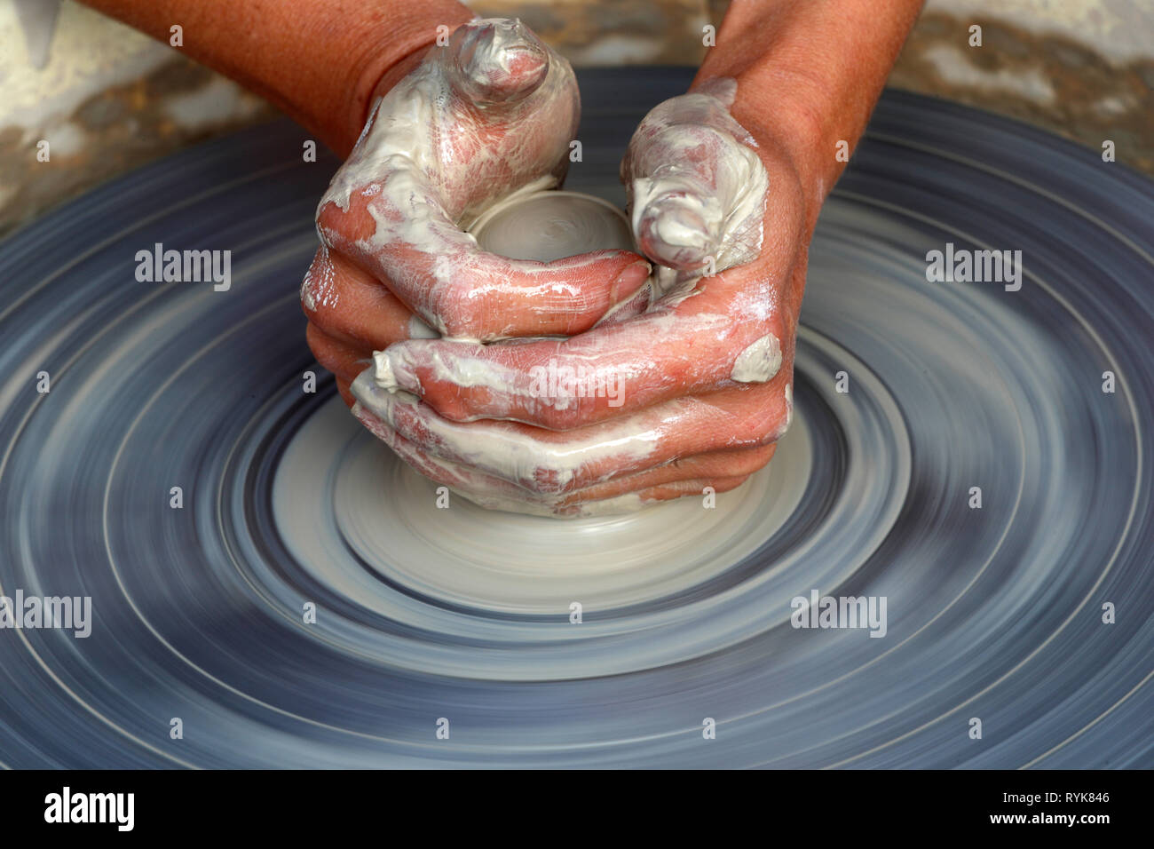Old Domancy craft festival. The hands of a potter shaping clay at a potters wheel.  France. - Stock Image