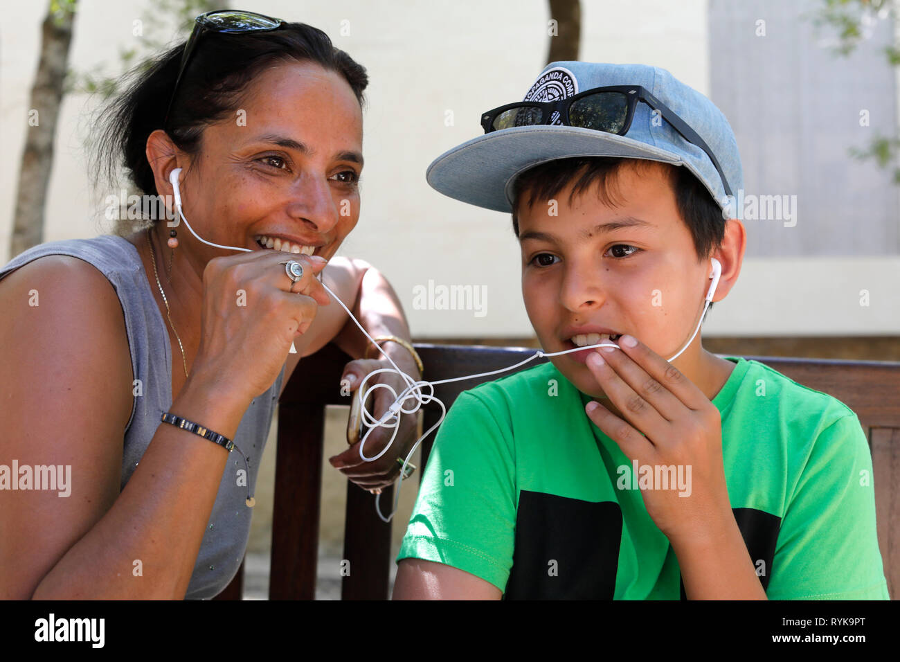 Mother and son having a cell phone conversation and sharing earphones in Sicily (Italy). - Stock Image