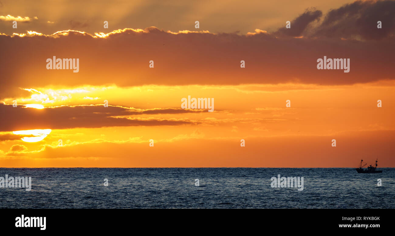 Fishing boat saling to the sun in the horizon at sunset - Stock Image