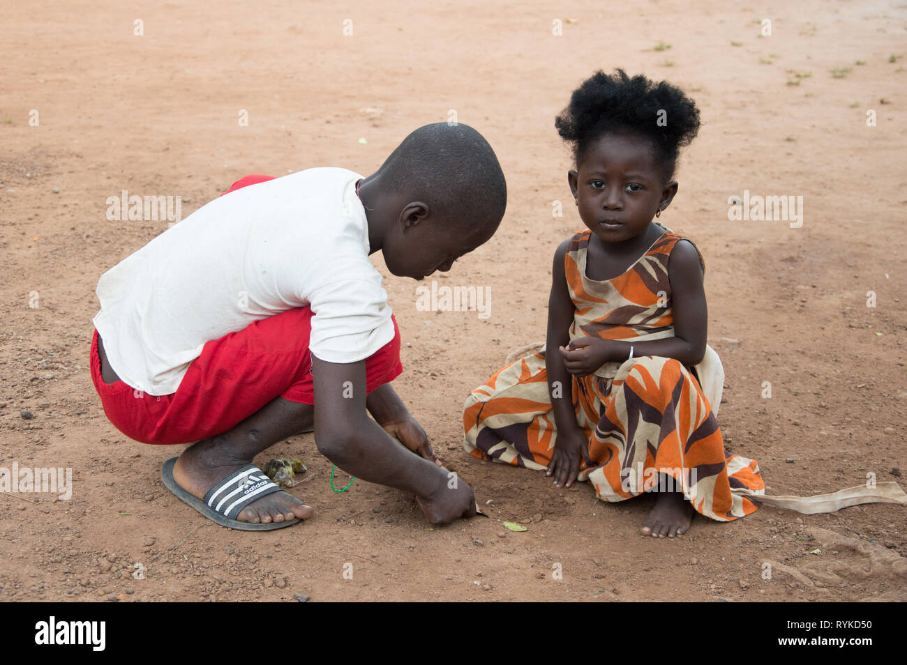Anekro, Ivory Coast - August 20, 2015: Two children play in the street, the two crouched, hands on the floor and the little girl looks at the camera Stock Photo
