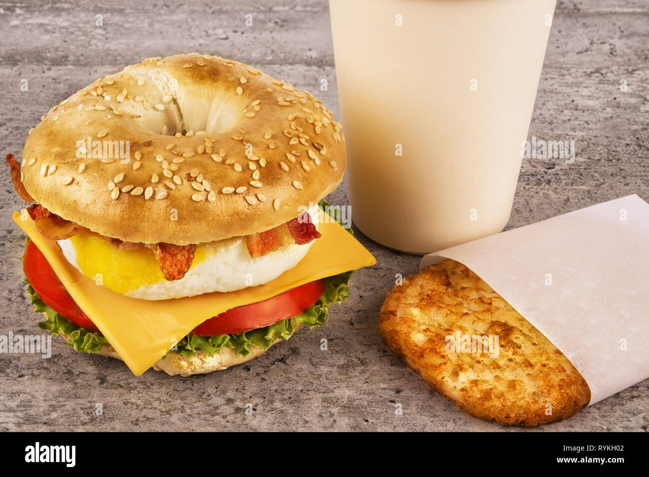 Breakfast Sandwich With Coffee And Hash Brown On Concrete Table Bagle Egg Cheese And Bacon Stock Photo Alamy
