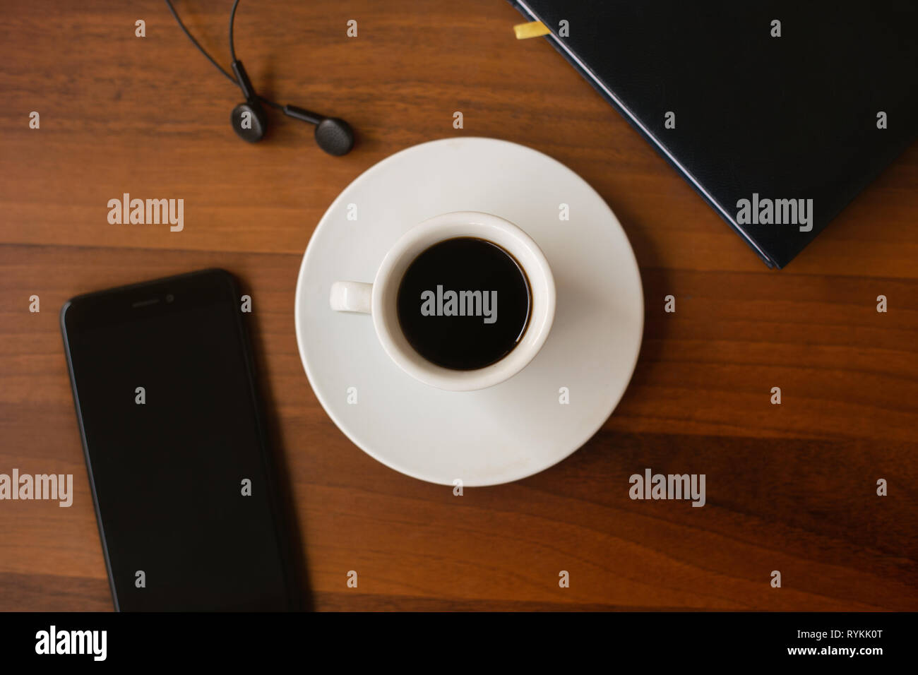 Top view Cup of Black Coffee (Espressino), Agenda, Earphones and Smartphone on a wooden table. Office Concept. - Stock Image