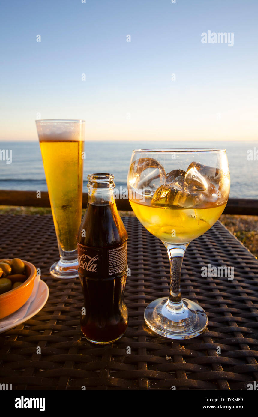 Glass of beer and a whiskey next to a Coca Cola on terrace with mediterranean sea in background. Spain. - Stock Image