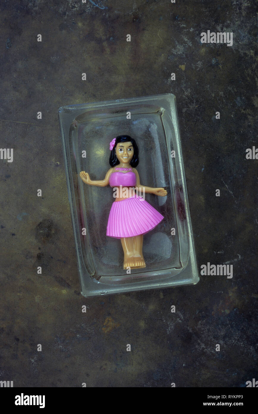 Plastic model of girl in pink skirt and top doing huila dance lying in glass dish - Stock Image