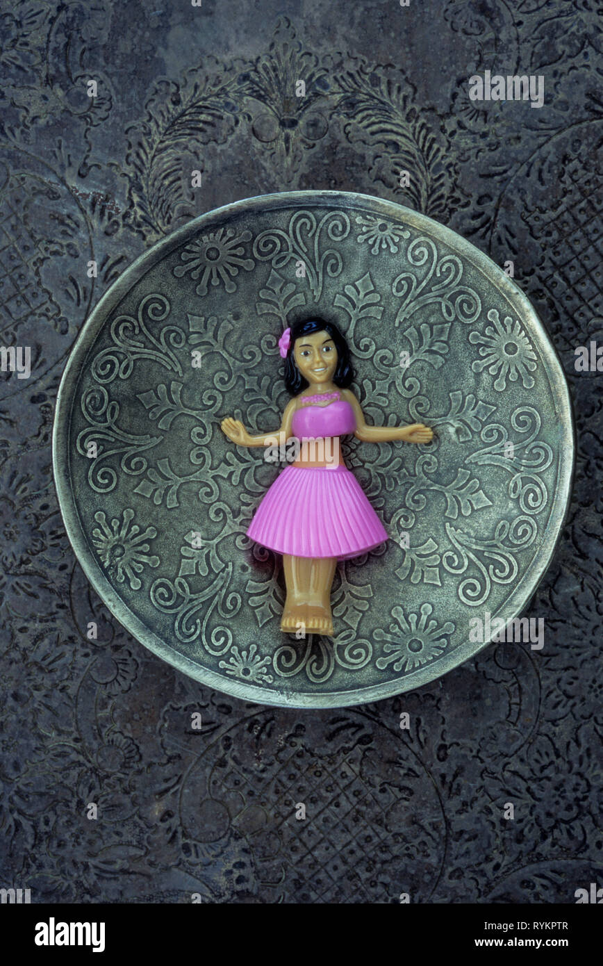 Plastic model of girl in pink skirt and top doing huila dance lying on patterned silver plate - Stock Image