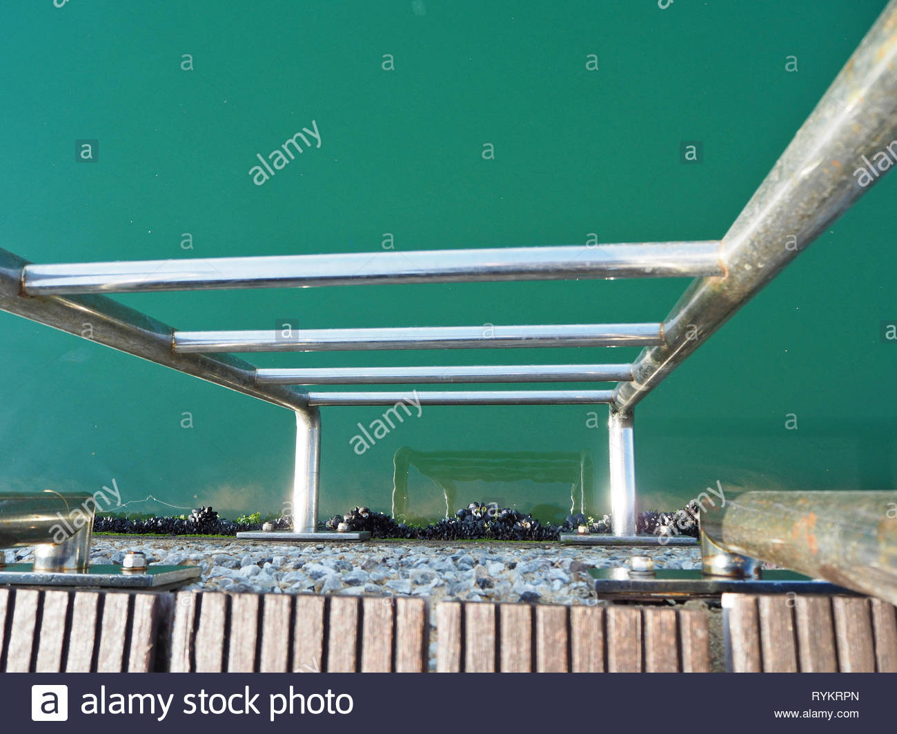 downwards view of a stainless steel stairway to the sea - Stock Image