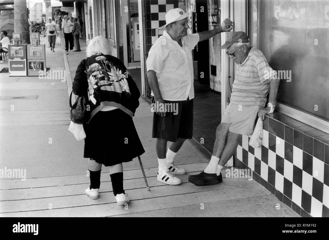 SENIORS SOUTH BEACH 1990S USA FLORIDA Two old men passing the time of day chatting while an old woman walks past using a walking stick South Beach Miami Florida 1990s 90s US HOMER SYKES Stock Photo
