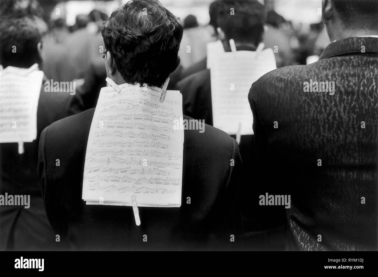Saints Days procession through the streets of New York. The ethnic  musician's walks down a midtown street. A musical score is attached to the jacket back of each member of the band with cloth pegs.  New York USA  1999. 1990s US HOMER SYKES. - Stock Image
