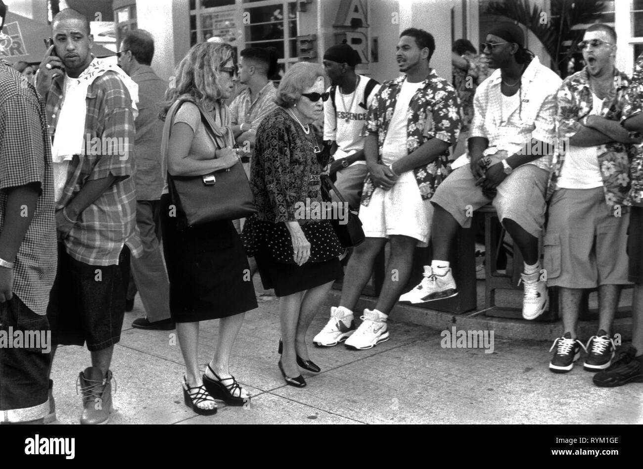 Two stressed looking business women push through a crowd of young men hanging out South Beach Miami Florida USA  1999 HOMER SYKES Stock Photo