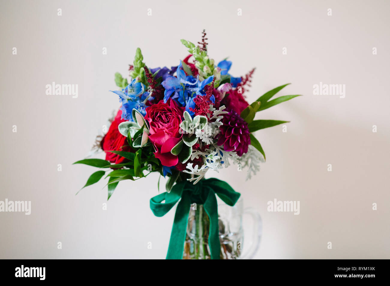 A vibrant colourful wedding flower bouquet on a plain background - Stock Image