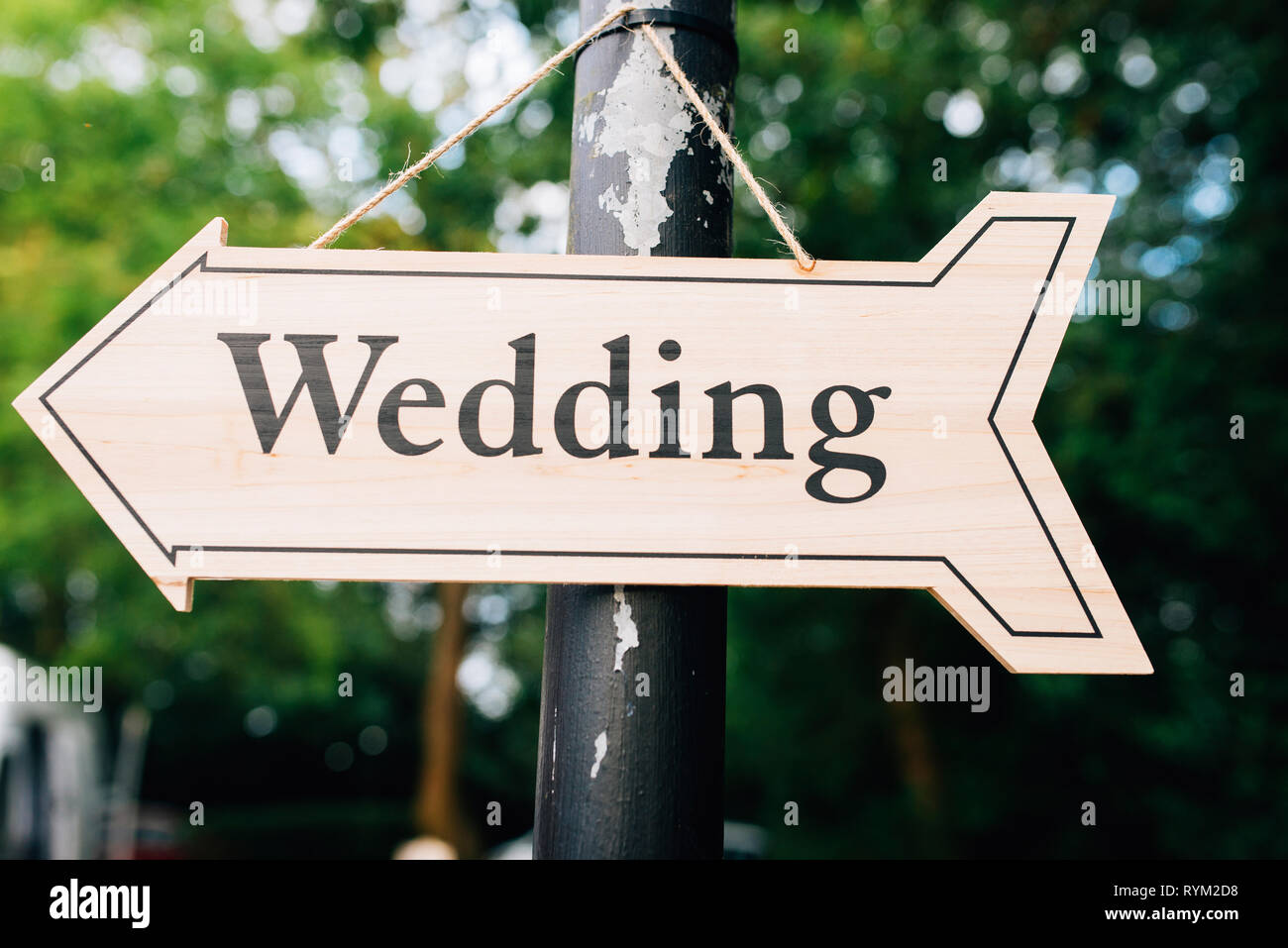 hanging wooden arrow with the word wedding written on it - Stock Image