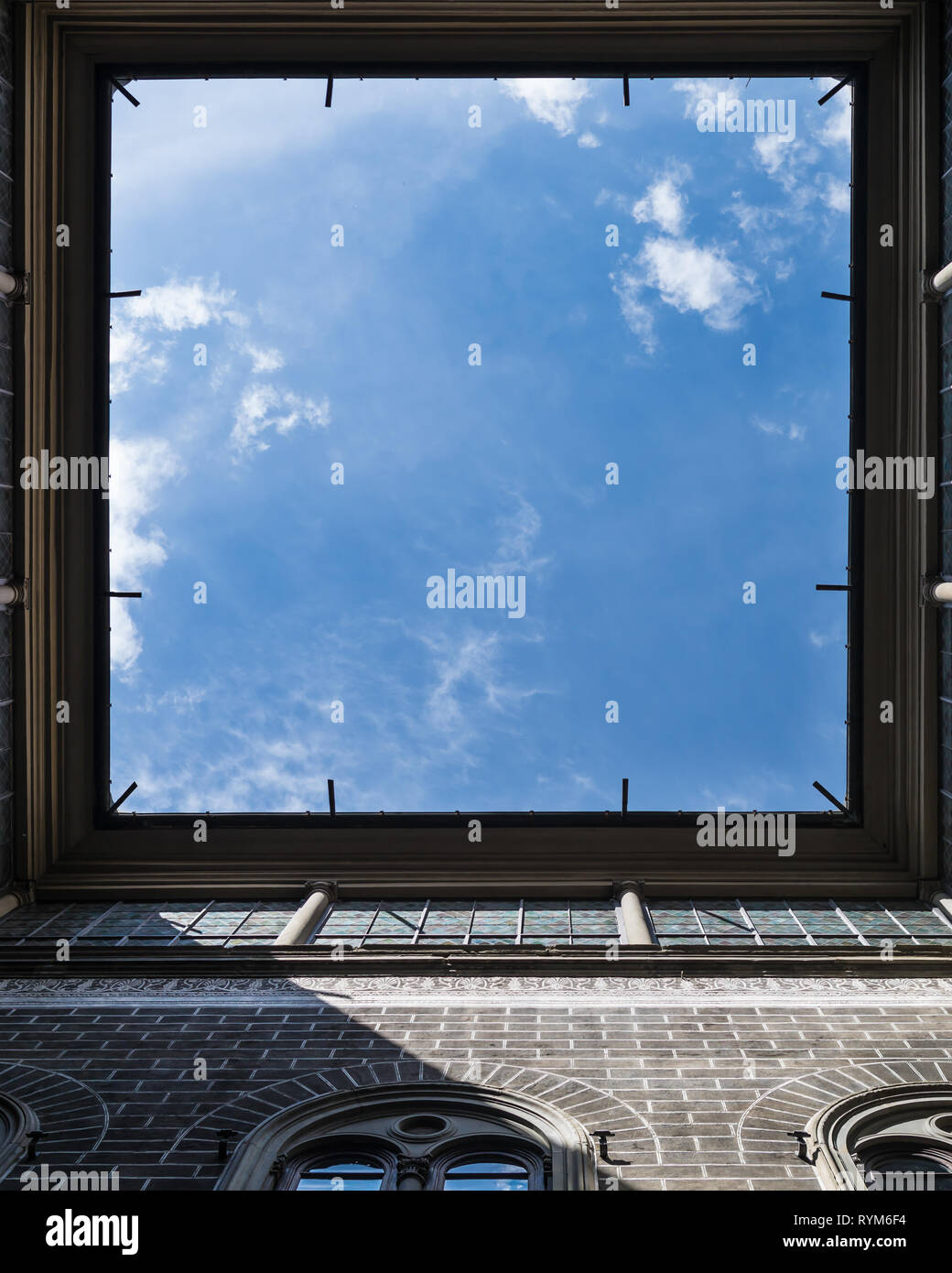 Window to the sky. View upstairs from courtyard of vintage house in Florence, Italy. Very interesting angle. Square frame with falling sun rays. Stock Photo