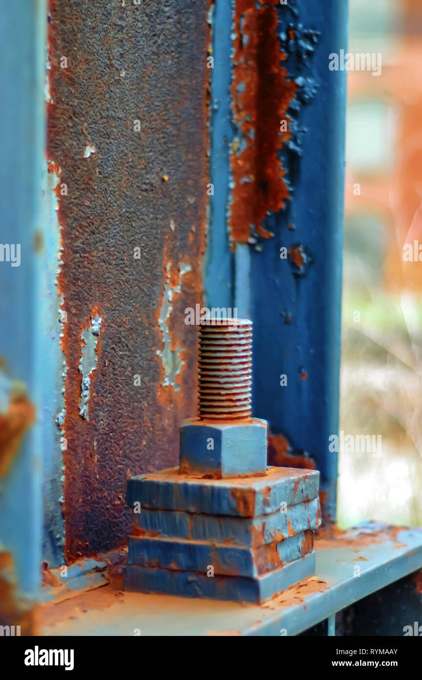 Paint peeling off a steel plate, nut and bolt of a railway signal gantry, causing them to rust and expose the texture of the metal plates. - Stock Image