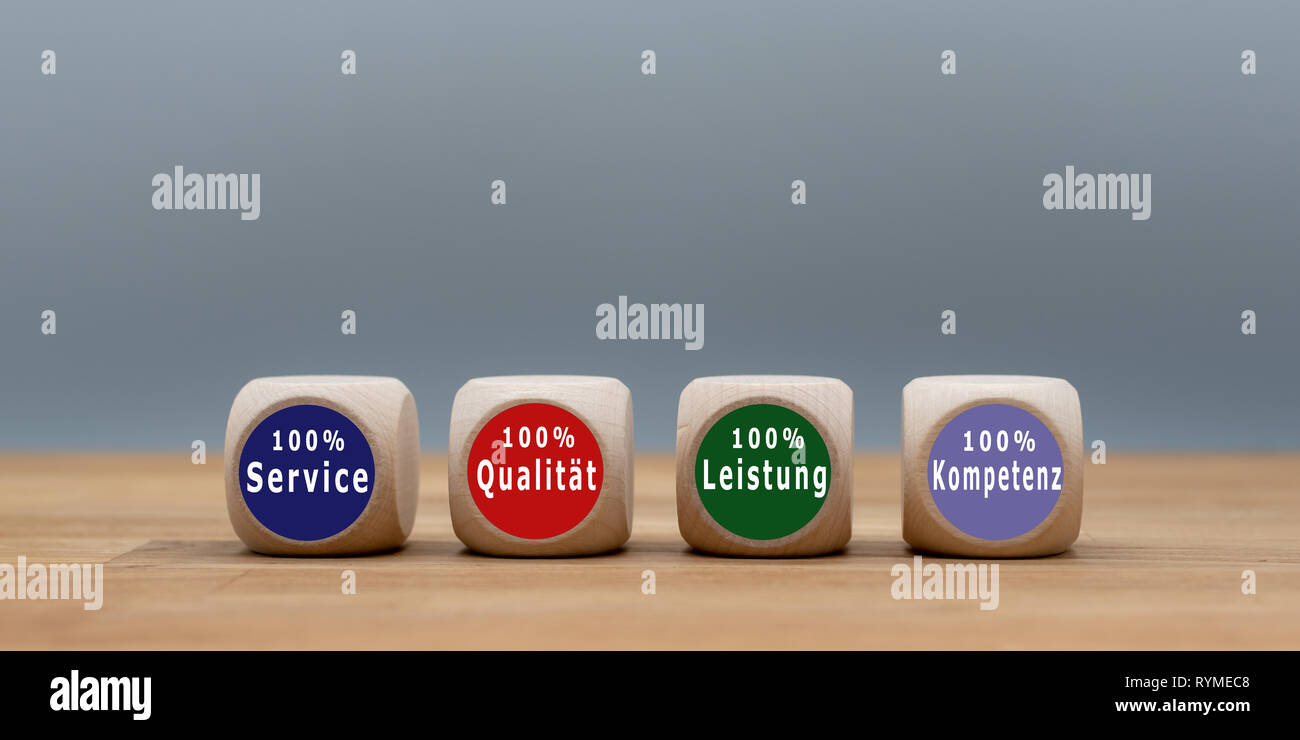 Four cubes with the German text '100% Service', '100% Qualität', '100% Leistung' ,'100% Kompetenz' ('100% Service', '100% Quality', '100% Performance' - Stock Image