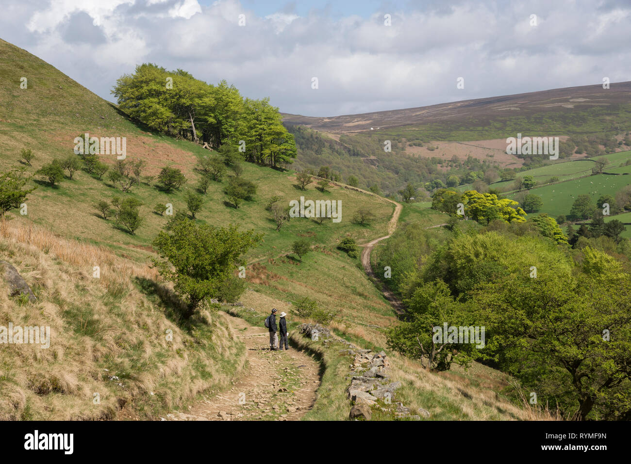 Couple standing to admire the view of the hills near Hayfield in the Peak District national park, Derbyshire, England. A sunny spring day. - Stock Image