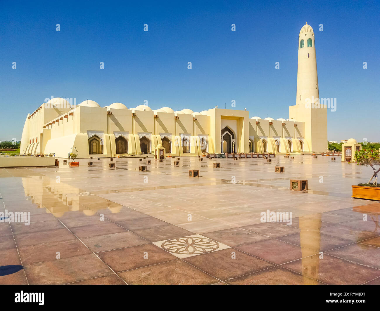 State Grand Mosque with a minaret reflecting on marble pavement outdoors. Doha mosque in Downtown, Qatar, Middle East, Arabian Peninsula. Morning Stock Photo