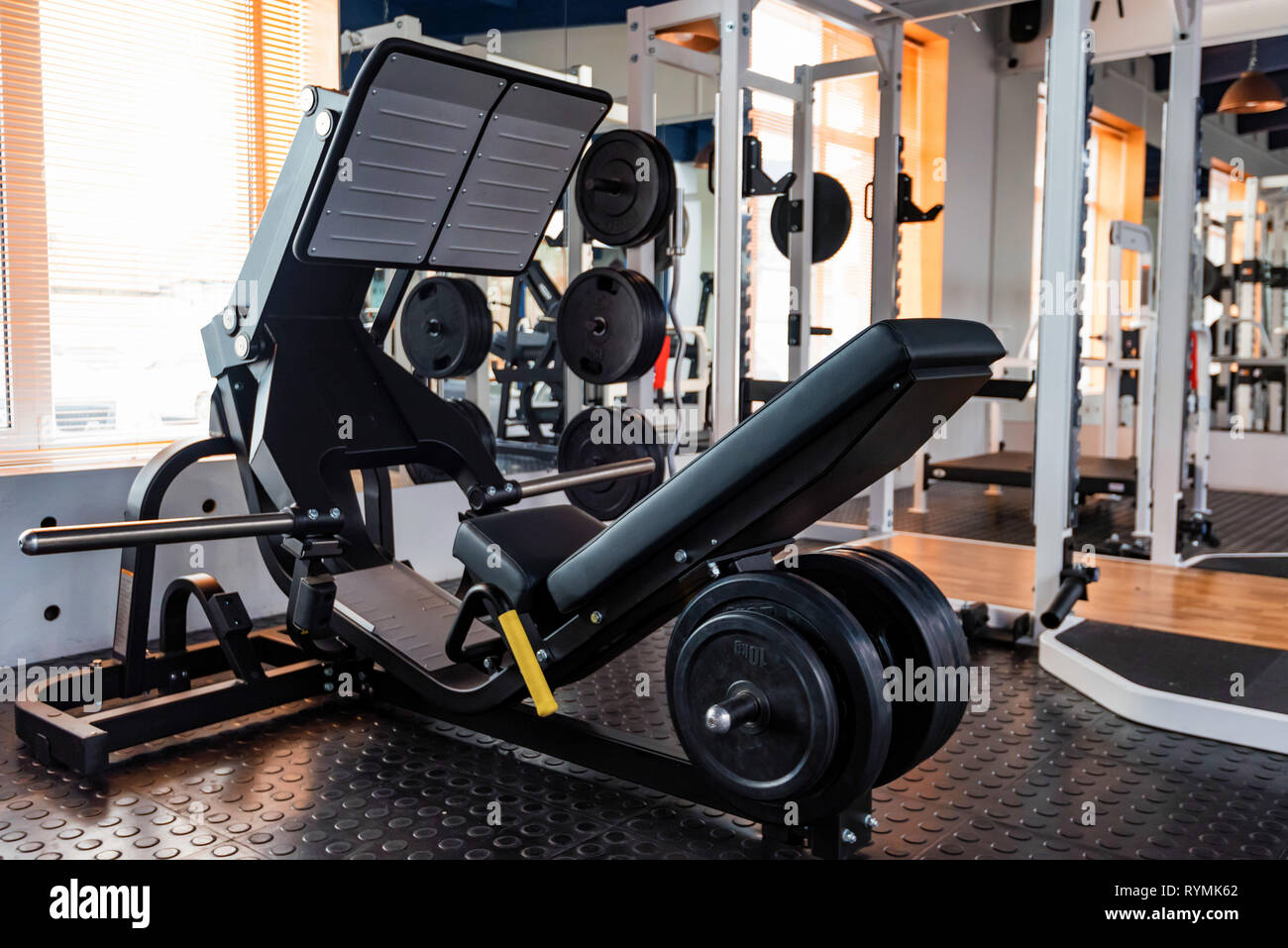 Empty leg press exercise machine in modern gym - Stock Image