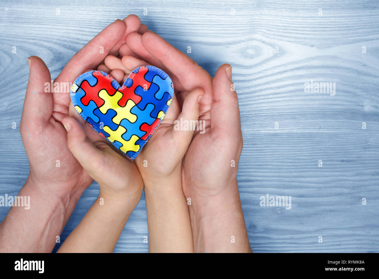 World Autism Awareness day, puzzle or jigsaw pattern on heart with autistic child's and father hands - Stock Image