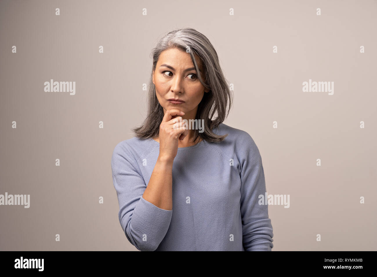 Asian woman is touching her chin thinking - Stock Image