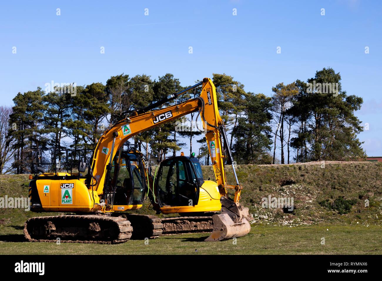 construction site excavators parked on grass area adjacent to building site - Stock Image