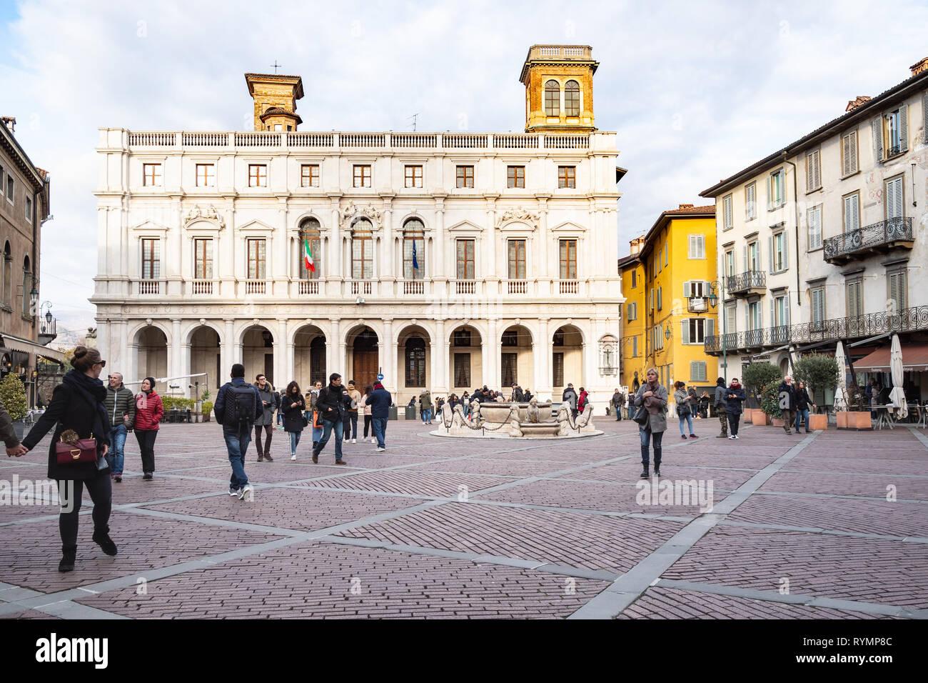 BERGAMO, ITALY - FEBRUARY 23, 2019: tourists on Piazza Vecchia square and view of Palazzo Nuova (public library Biblioteca Civica Angelo Mai) in Citta Stock Photo