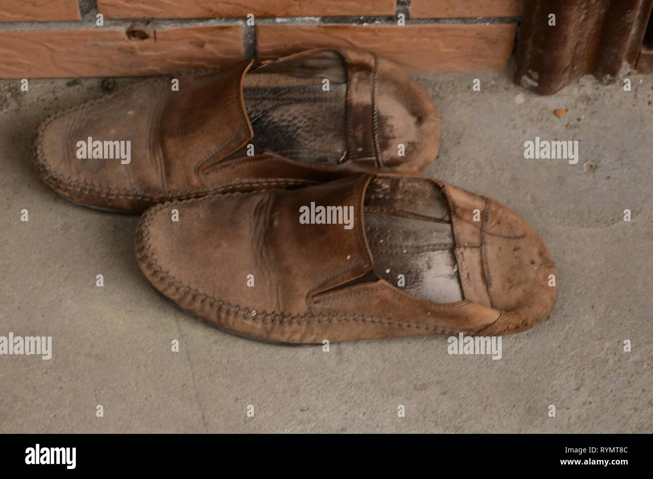 old brown leather shoes waiting to be polished - Stock Image
