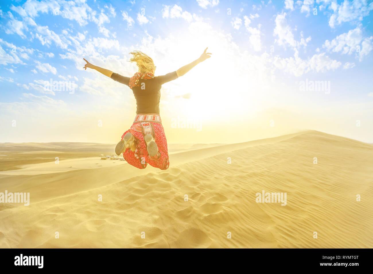 Inland sea landscape, a major tourist destination for Qatar. Woman traveler jumping on sand dunes in Qatar desert at sunset. Happy caucasian tourist - Stock Image