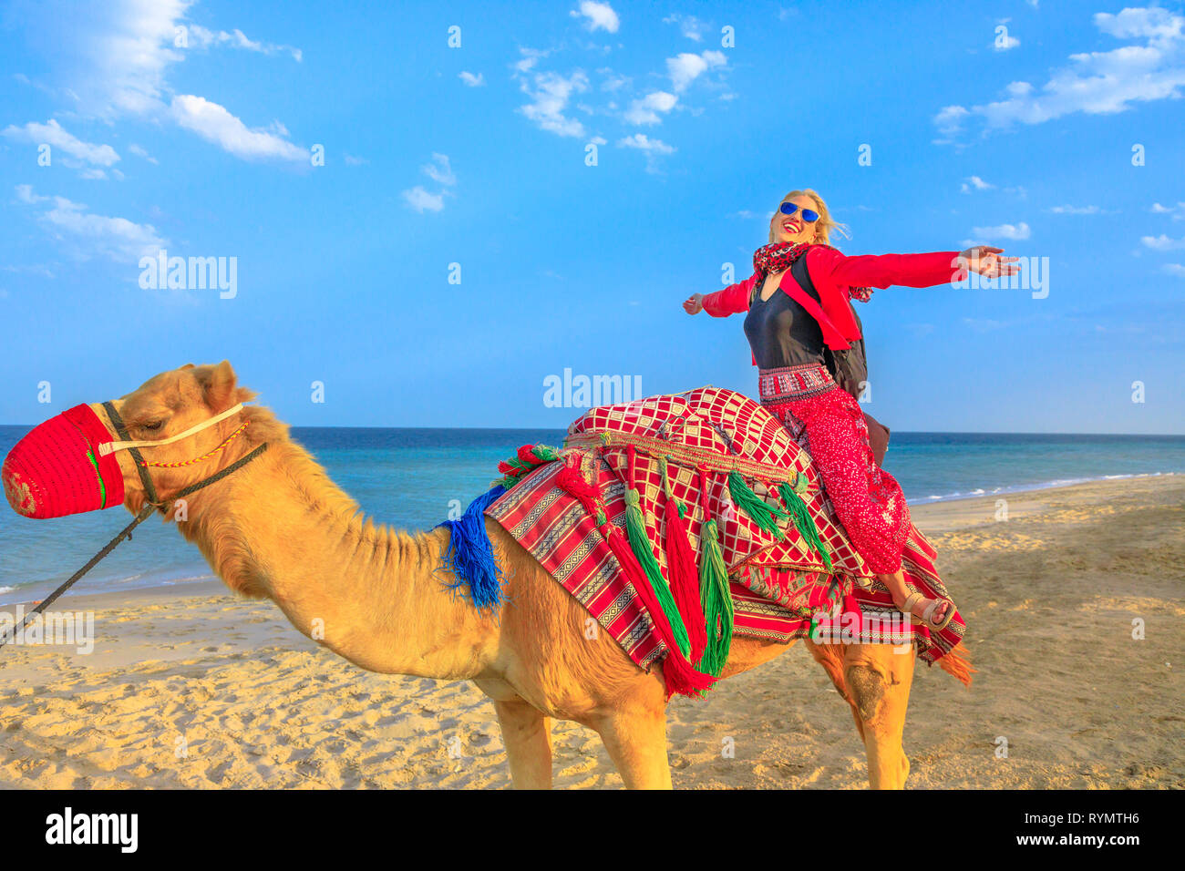 Inland sea is a major tourist destination for Qatar. Freedom woman riding camel on beach at Khor al Udaid in Persian Gulf. Caucasian blonde tourist - Stock Image