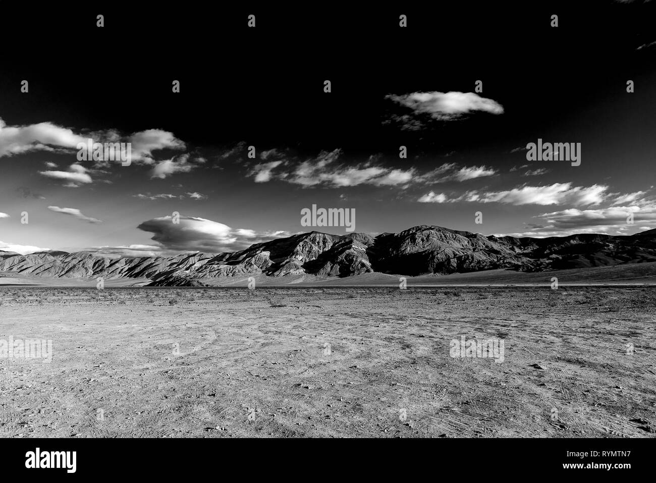 Black and white, barren desert valley and mountains with dark sky and white clouds. - Stock Image
