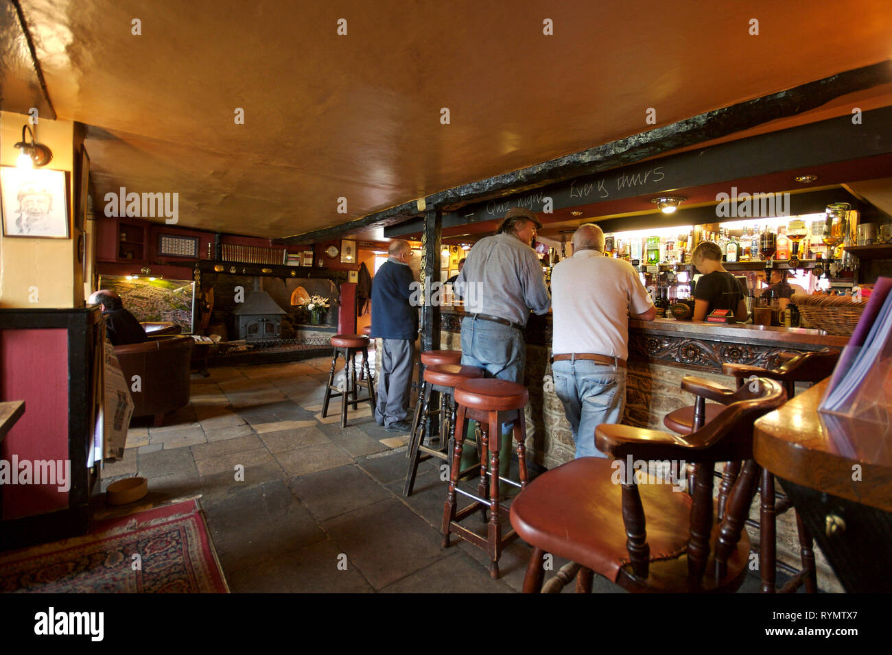 English village pub interior with customers at the bar - Stock Image