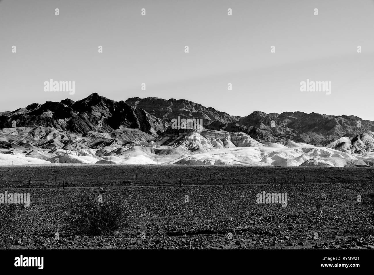 Black and white, Death Valley California with sparse vegetation, dark rocky fields gives way to white hills and barren desert mountains. - Stock Image