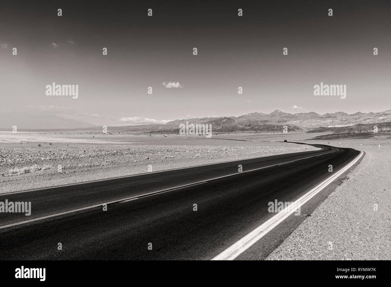 Paved road curving through the barren desert towards mountains in the distance. Black and white. - Stock Image
