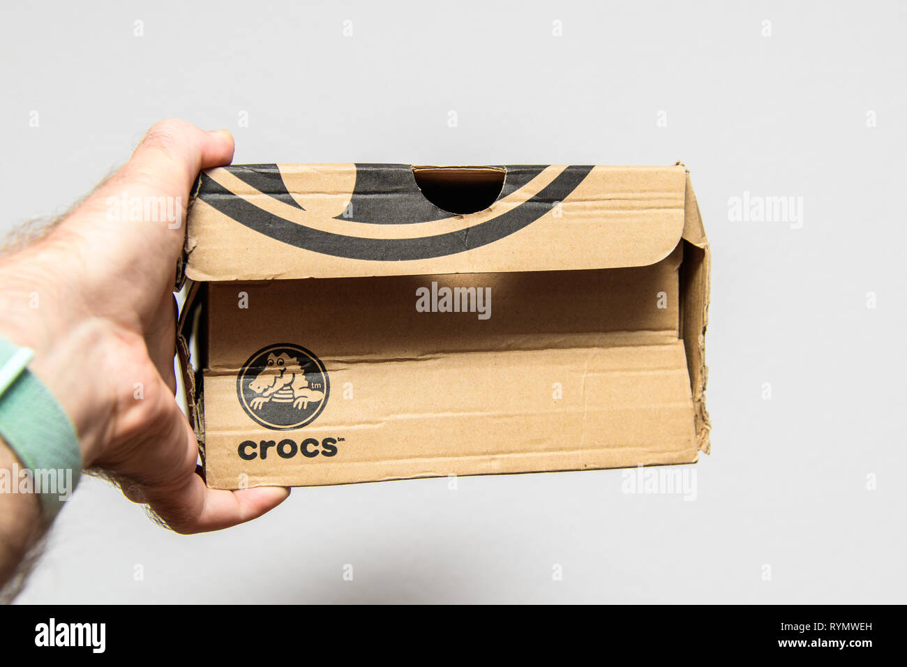 Paris, France - Jun 12, 2018: Freshly delivered Crocs shoes cardboard box featuring big crocodile logotype - side view of the box in man's hands  - Stock Image