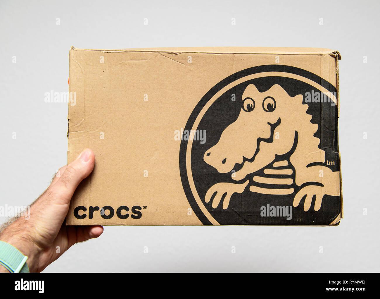 Paris, France - Jun 12, 2018: Man hand holding Freshly delivered Crocs shoes cardboard box featuring big crocodile logotype white background - Stock Image